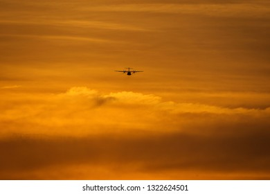 Small plane in the middle of the red clouds at sunset