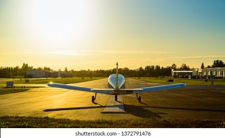 Small plane ready to take off at the airport at sunrise.