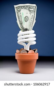 Small plant pot with a fluorescent light bulb a dollar and few dimes and pennies with a blue background