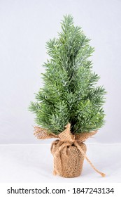 a small plastic christmas tree in a pot