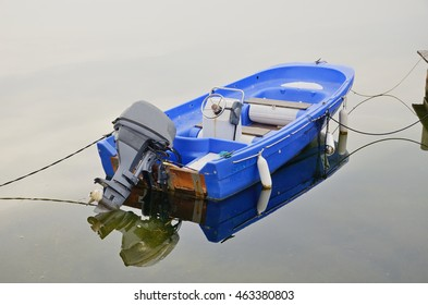 The small plastic motorized watercraft is fixed on the still water surface.