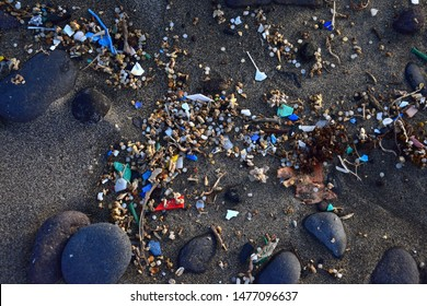 Small plastic parts and microplastics in the sand of Famara beach, Lanzarote, Spain.
