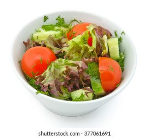 Small plate of inflight meal, salad with tomatoes and cucumbers on a white background