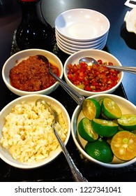 Small plates of condiments to make a meal, especially hot pot, more flavorful - chopped garlic, chili paste, chopped chili, calamansi, and soy sauce. With a stack of empty sauce dishes at the side.