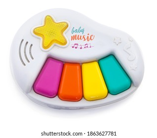 small play toy for children. Miniature piano with four keys, for creating simple melodies. Plastic toy emitting tones. Isolated on white background with shadow reflection. Top view. Studio shot.