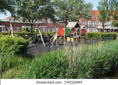 A small playground with a climbing house, swing and bench in a new residential area in the Dutch village in Egmond aan den Hoef.