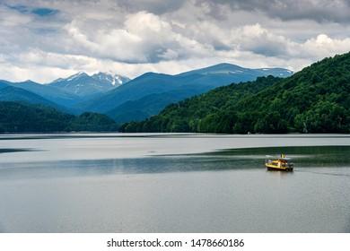 A small pleasure boat crosses the Vidraru Reservoir in the Carpathian Mountains, Transfagarasan (Romania).