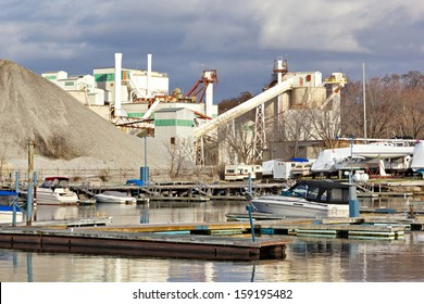 A small pleasure craft marina for boating fun sits in the shadow of industry on the water front, trying to share the space for fun.
