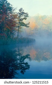 Small pond with trees in fall color reflecting through the mist