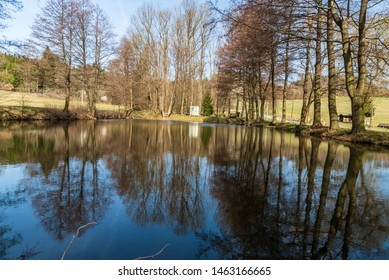 small pond with trees mirroring on water ground and clear sky near Hvozd village not far from Javoricske jeskyne cave and Bouzov castle in Czech republic