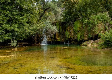 A small pond with a small waterfall. A lake with crystal clear water surrounded by green trees and bushes. In the background a small waterfall. Main colors: green and yellow.
