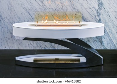 small portable fashionable fireplace, white modern fireplace on a background of marble wall