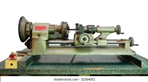 Small portable metal lathe on green board isolated