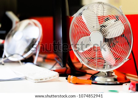 Small, portable switched off fan on desk in office. Horizotal close up, low angle perspective from desk level