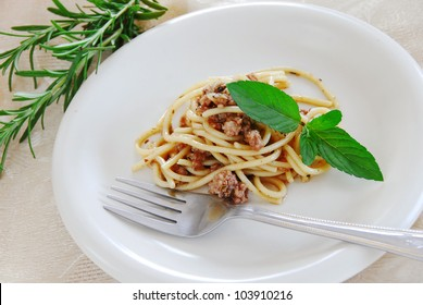 small portion of spaghetti mixed with minced meat served on white plate