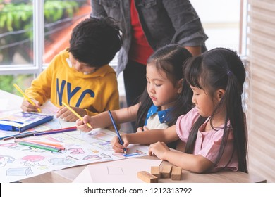 Small Pre School Student kids color painting on paper in Art group classroom in a Playroom with a Teacher guiding on the Background, for children day school education concept