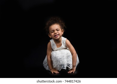 Small preschooler African american kid sitting on her hunkers in white dress and grimacing isolated on black
