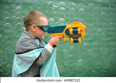 Small preschooler boy with blaster prepare for attack and play with friends in protective glasses. Excited Child with darts toy gun on the play field