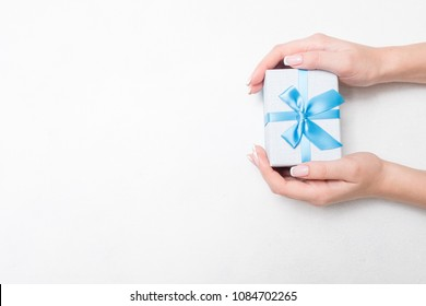 small present with blue ribbon bow in woman hands on white background. Sweet reward gift for holiday or birthday. free space concept
