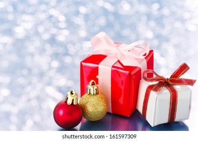 Small presents on white sparkle background. Small presents and Christmas balls on snowing background.