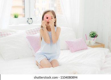 Small pretty female child holds tasty sweet doughnut, poses in bedroom on comfortabled bed, dressed in pyjamas, going to have breakfast, has joy and poses at camera. Chilhood and bedding concept