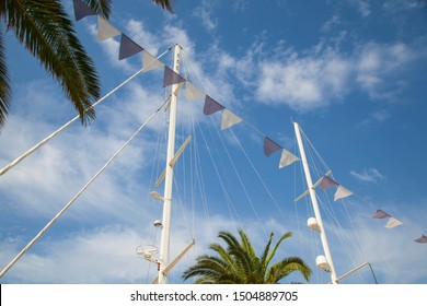 small pretty festive flags are waving on the wind with sailing ship masts and blue sky as a background, sunny day nautical backdrop
