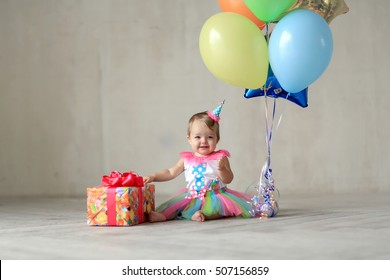 small pritsessa with a cap on his head and a fluffy skirt sitting on the floor next to the balloons and a great gift, celebrating its first birthday