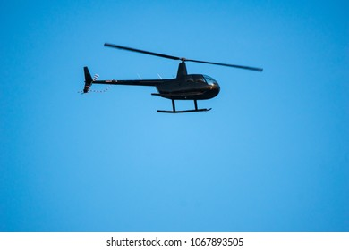 A small private helicopter in the ble sky