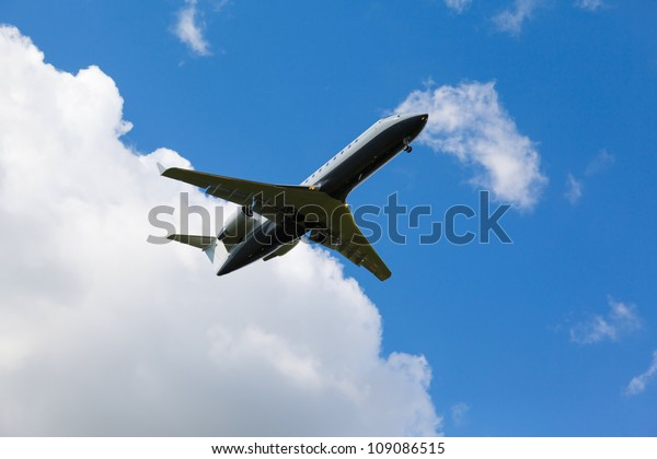 small private jet comes in to land with gear againstblue sky