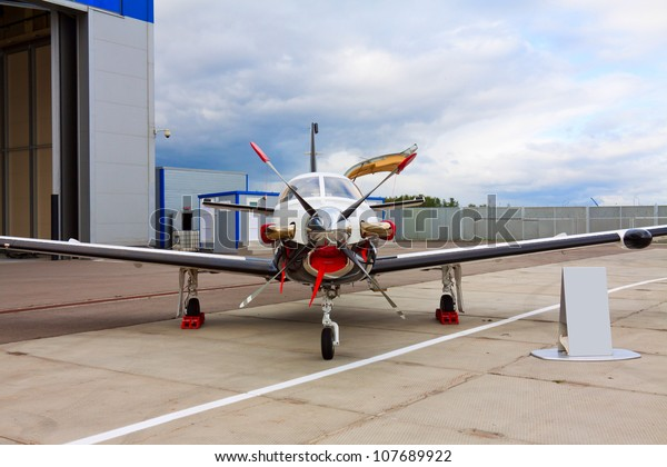 small private propeller aircraft with one engine on background of hangar in cloudy weather