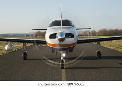 Small private single-engine piston aircraft on runway, front view