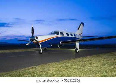 Small private single-engine piston aircraft on runway during sunset