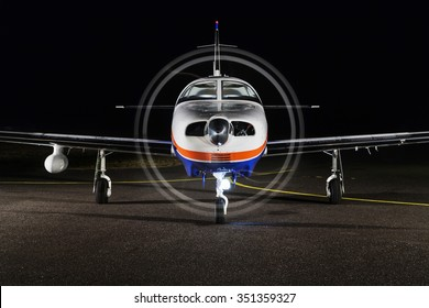 Small private single-engine piston aircraft on runway, front view, night photo