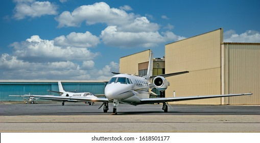 A small private white jet at an airport