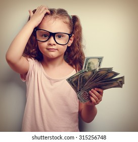 Small professor in eye glasses scratching head, holding money and thinking how earring more. Kid have a big idea. Emotional closeup vintage portrait