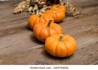 Small Pumpkins and Dry Bouquet of Flowers on a Rustic Wooden Table