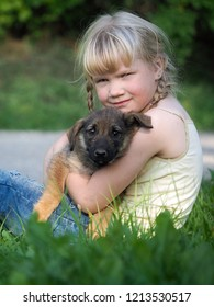 A small puppy and child sitting on the grass. Girl hugging a dog