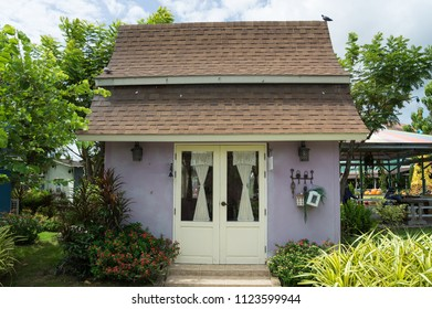 A small purple home with a white door and green garden