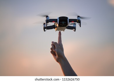 A small quadcopter model hovering in the air over a pointing finger against colorful evening sky.