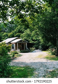 A small, quaint, wooden cabin is shown among green trees in rural Kentucky farmland