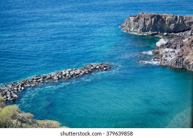 A small quiet Cove with a breakwater. The crystal clear turquoise water of the ocean