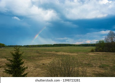 A small rainbow against the dark sky over a dense forest and a large field.