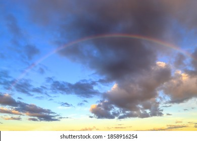 Small rainbow in the morning sky at dawn against the background of cumulus clouds