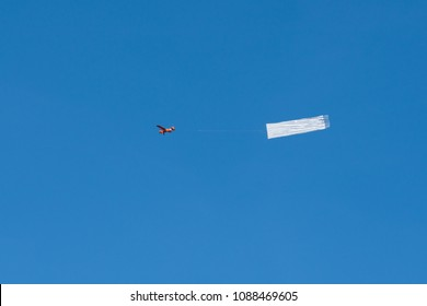 A small red airplane is pulling a white banner in the blue sky.