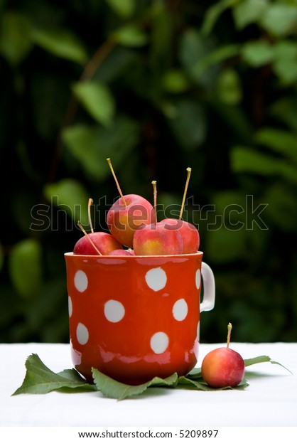 Small red apples in the cup