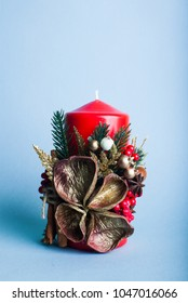 Small red candle with decoratiions on blur ble background