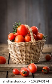 Small red cherry tomatoes  in a small wicker basket  on wooden table. Healthy organic food. Tomato harvest