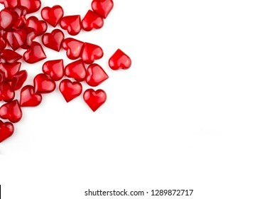 A lot of small red clear crystal shiny Valentine hearts on white background top view with copyspace