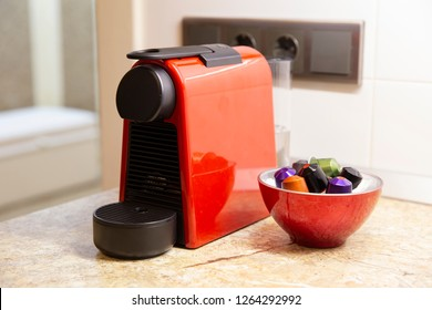 A small red coffee machine with colored capsules on a kitchen counter