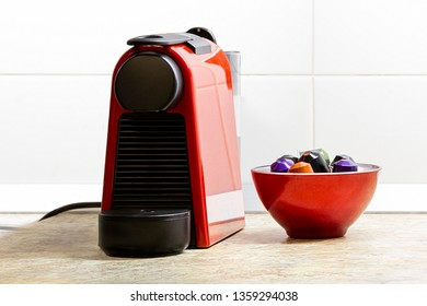 Small red coffee machine with colorful capsules